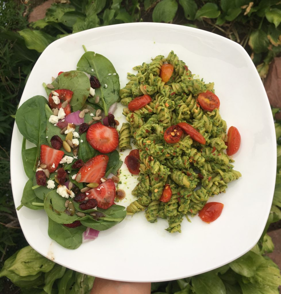 Chickpea pasta with pesto and tomatoes and a spinach and strawberry salad