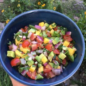 Avocado Mango Salsa in blue bowl with garden background
