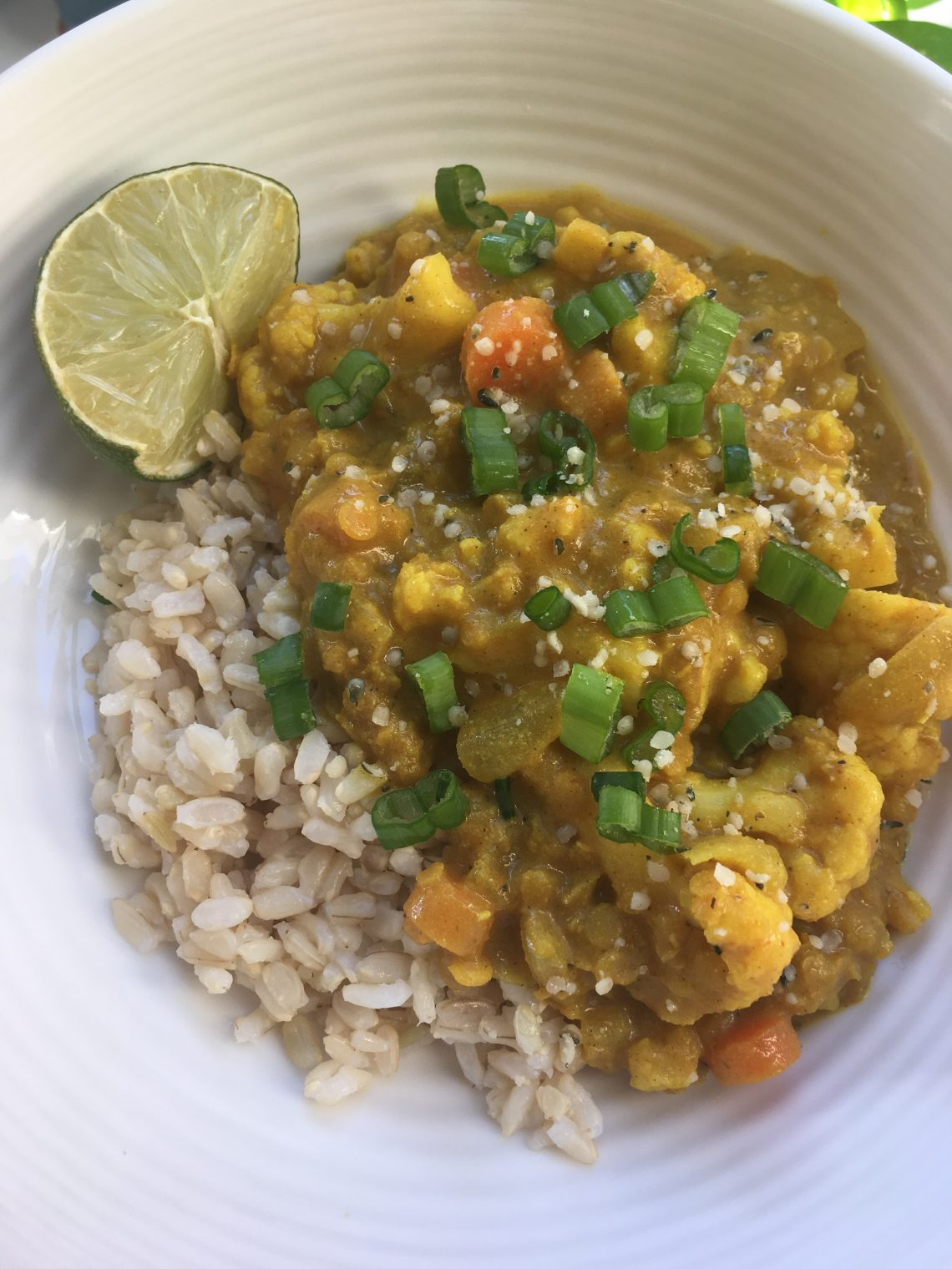 Red Lentil and Cauliflower Curry with brown rice in a white bowl