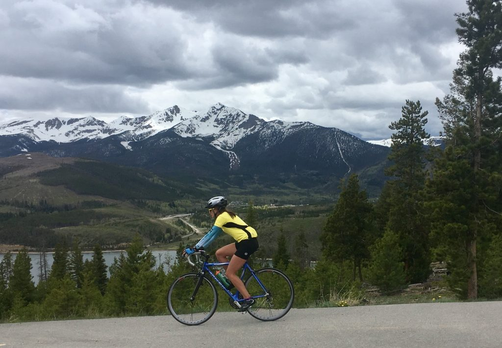 girl riding road bike with mountains in the background